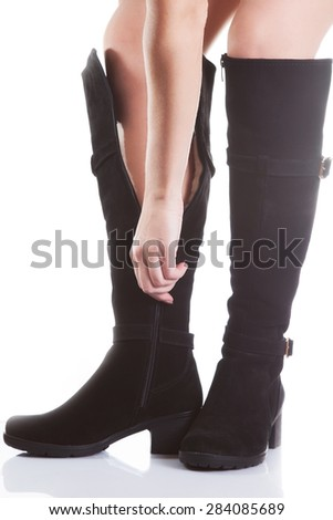 Beautiful female legs in black suede boots on a white background. hand buttons zipper - stock photo