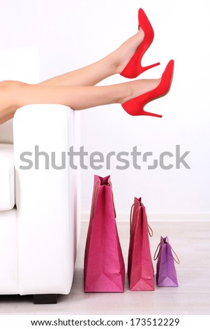 Beautiful female legs in red shoes on sofa with shopping bags on white background - stock photo