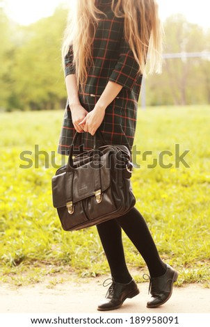 Beautiful female legs in shoes Oxford with a big bag - stock photo
