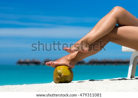 Beautiful female legs in the tropical beach conceptual image of vacation