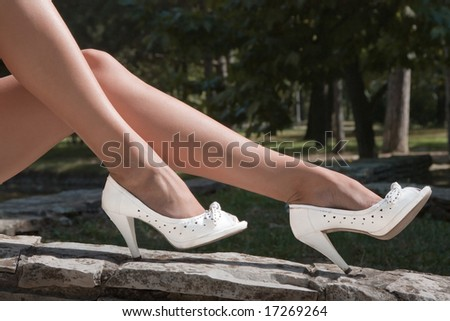 beautiful female legs in white shoes