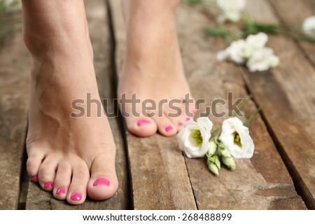 Beautiful female legs on rustic wooden floor background - stock photo
