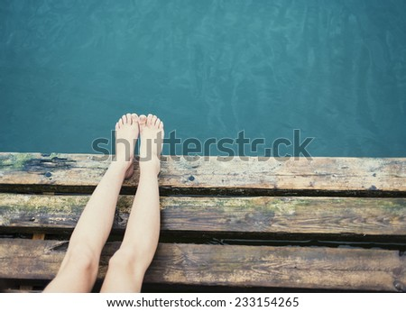 Beautiful female legs on the pier near the sea - stock photo