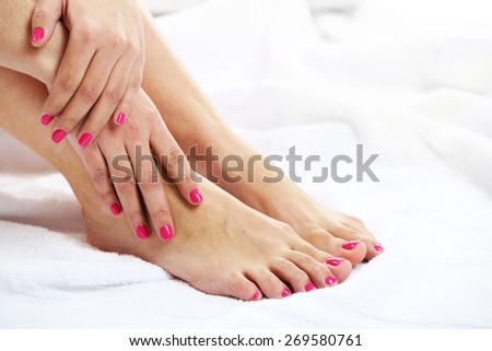 Beautiful female legs on towel, on light background