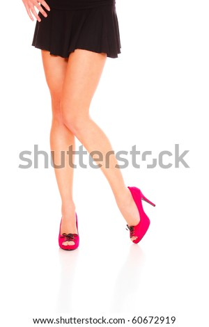 Beautiful female legs wearing red shoes over white background