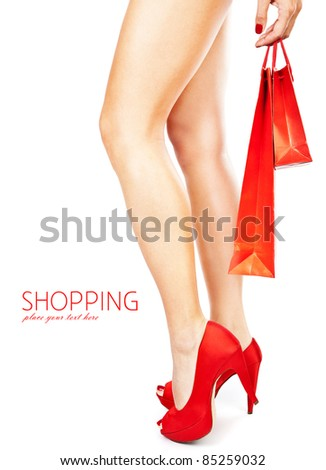 Beautiful female legs with red high heels holding shopping bags isolated on white background, money spending concept - stock photo