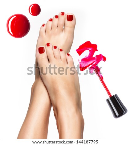 Beautiful female legs with red pedicure and  nail polish  bottle with  brush - stock photo