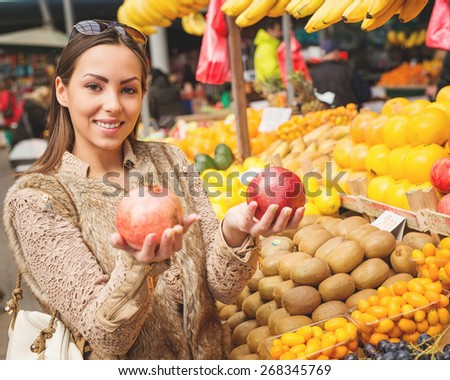 Beautiful female looking for fresh fruits at marketplace. Pomegranate. Shallow depth of field. - stock photo