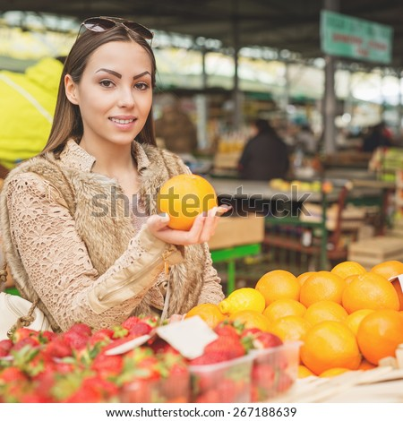 Beautiful female looking for fresh fruits ready for sale at marketplace.  - stock photo