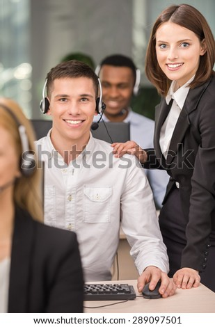 Beautiful female manager helping call centre agent.