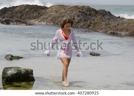 Beautiful female model in bikini and shirt walking in the water at the beach - stock photo