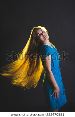 Beautiful female model in blue dress posing at studio in the light flashes on black background. Attractive cute girl with long sun-drenched blowing and  flying flaming hair. - stock photo