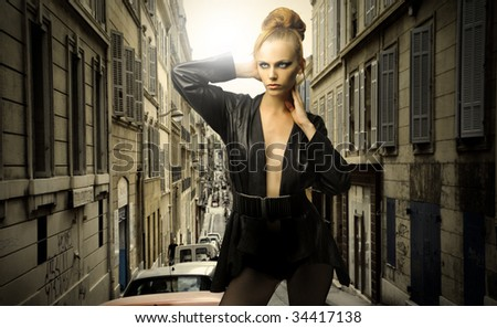 beautiful female model in elegant clothes against a cityscape - stock photo