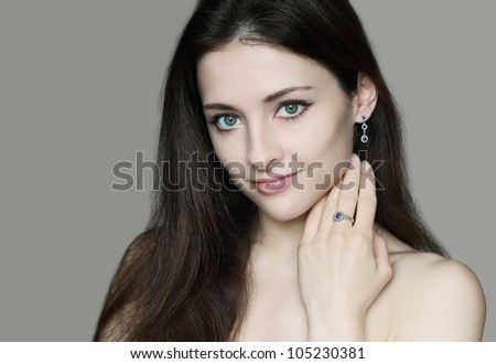 Beautiful female model in jewelry looking. Beauty portrait isolated on grey background - stock photo