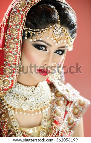 Beautiful female model in traditional indian bride costume with makeup and jewellery - stock photo
