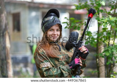 Beautiful female model posing in paintball ammunition outdoors - stock photo