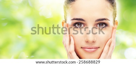 Beautiful female model touching her smooth glowing face skin and smiling at camera - stock photo