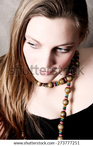 Beautiful female model wearing wooden beads and black top - stock photo
