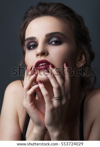 Beautiful female model with an evening makeup and hairstyle on the grey background. Studio portrait.