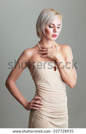 beautiful female model with blond hair in beige dress - stock photo