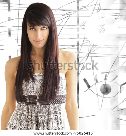 Beautiful female model with long dark hair in pretty dress against modern abstract background - stock photo