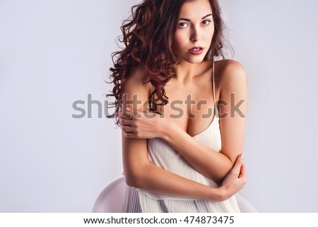 Beautiful female model with makeup and curly hair. Fashion photo.