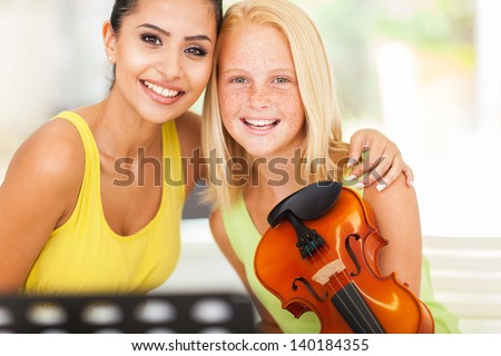 beautiful female music teacher with violin student - stock photo