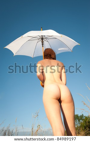 Beautiful female nudist walking to the beach with white umbrella under deep blue sky - stock photo