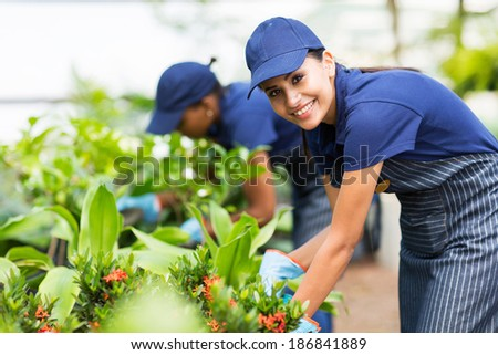 beautiful female nursery worker trimming plants - stock photo