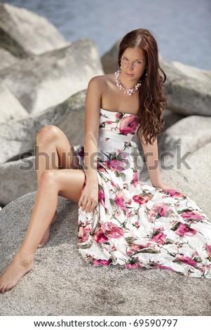 Beautiful female on beach rocks - stock photo