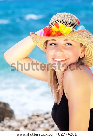 Beautiful female outdoor portrait over blue beach water, happy smiling face, summer fun concept - stock photo