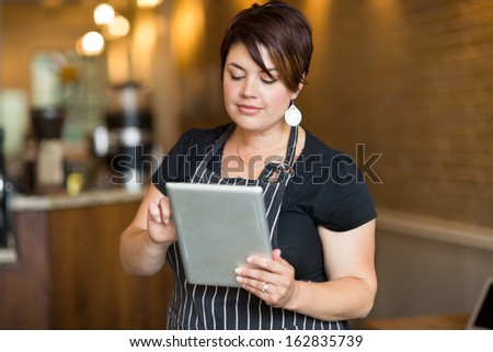 Beautiful female owner using digital tablet in cafe - stock photo