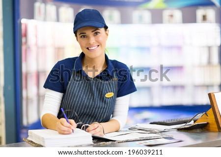 beautiful female paint store clerk working - stock photo