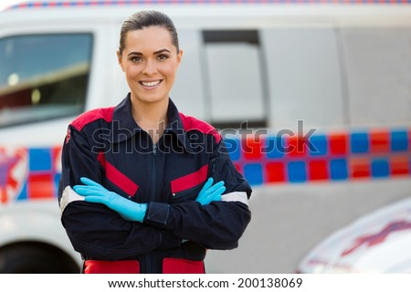 beautiful female paramedic with arms crossed in front of ambulance - stock photo