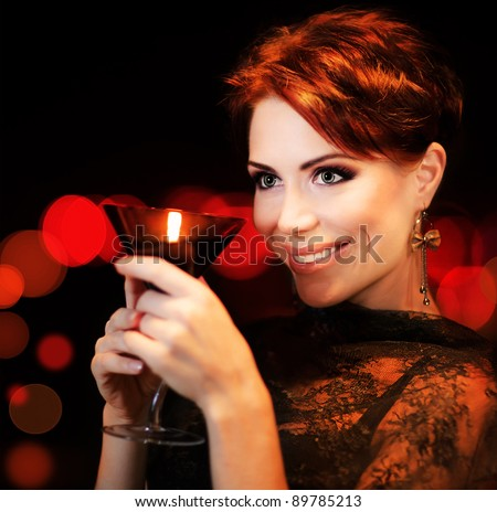 Beautiful female partying, celebrating holiday, portrait of a woman holding martini glass, girl over black background with red blur bokeh lights, luxury nightlife - stock photo