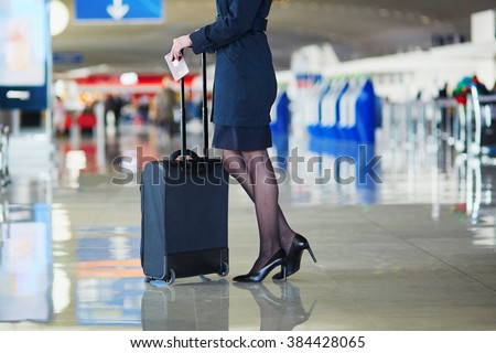 Beautiful female passenger or flight attendant in international airport with hand luggage - stock photo