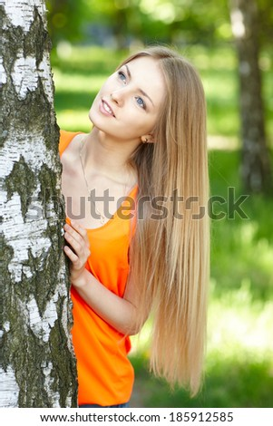 Beautiful female peeping from behind tree and looking up, against green of summer park. - stock photo