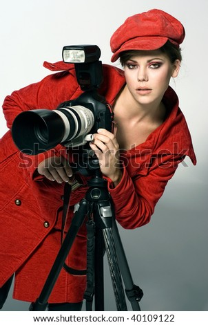 Beautiful female photographer in red clothing - stock photo