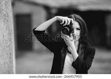 Beautiful female photographer posing with camera - stock photo