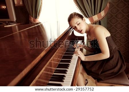 beautiful female pianist playing piano - stock photo