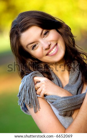beautiful female portrait outdoors smiling and playing with her scarf - stock photo