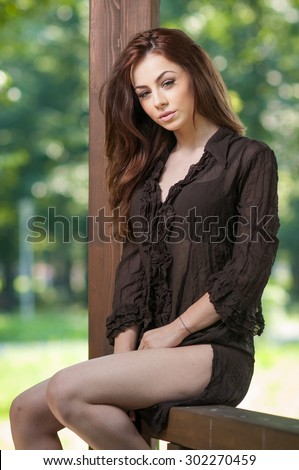 Beautiful female portrait with long brown hair outdoor. Genuine natural brunette with gorgeous eyes posing in park. Portrait of a attractive woman with black dress sitting on a wooden pavilion  - stock photo