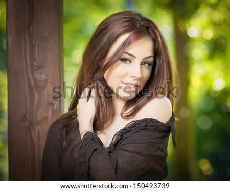 Beautiful female portrait with long brown hair outdoor. Genuine natural brunette with long hair in park. Portrait of a attractive woman with beautiful eyes and black blouse near a tree - stock photo