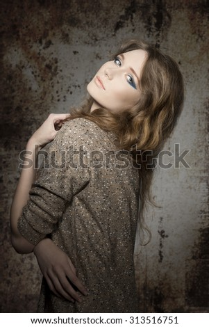 beautiful female posing in fall fashion shoot with long wavy hair, blue stylish make-up and casual sweater, in sensual pose looking in camera  - stock photo