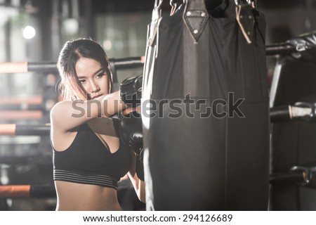 Beautiful Female Punching A Boxing bag With Boxing Gloves at the gym. concept about sport, fitness, martial arts and people - stock photo