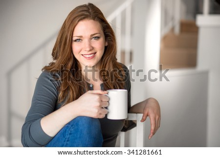 Beautiful female relaxed with cup of tea coffee indoor blonde head shot space modern interior living staircase