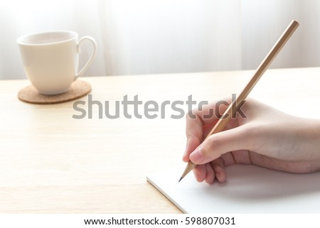 beautiful female's hand holding pencil above a notebook paper with a cup of tea