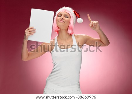 Beautiful female santa in pink wig holding a christmas clear white card over red background - stock photo