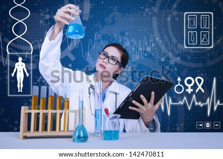 Beautiful female scientist analyzing solution on blue background - stock photo
