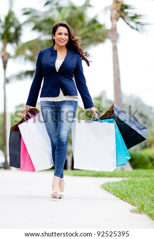Beautiful female shopper with bags walking outdoors - stock photo